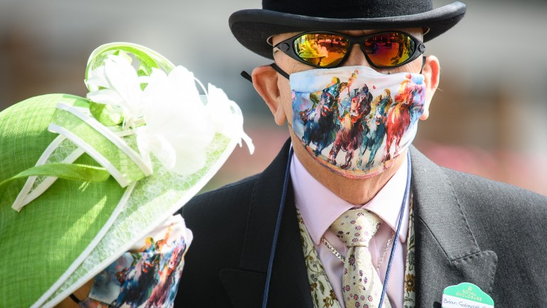 Racing-inspired face masks are sported by two racegoers