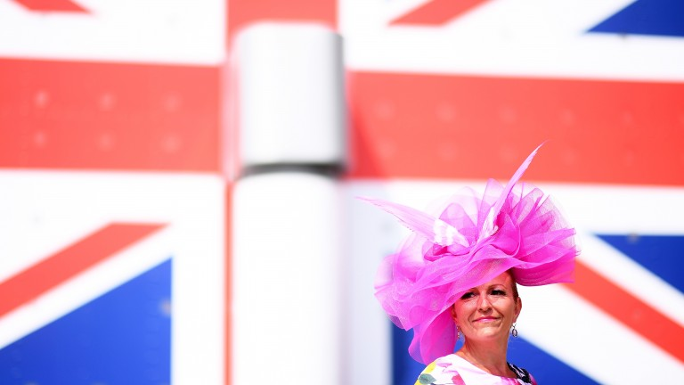 A racegoer stands in front of the Union Jack flag on the stand
