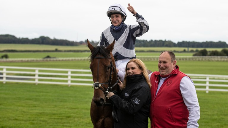 Moyglare Stakes heroine Discoveries is greeted by groom Aoife McLoughlin and travelling head lad Niall 'Bubba' Amond